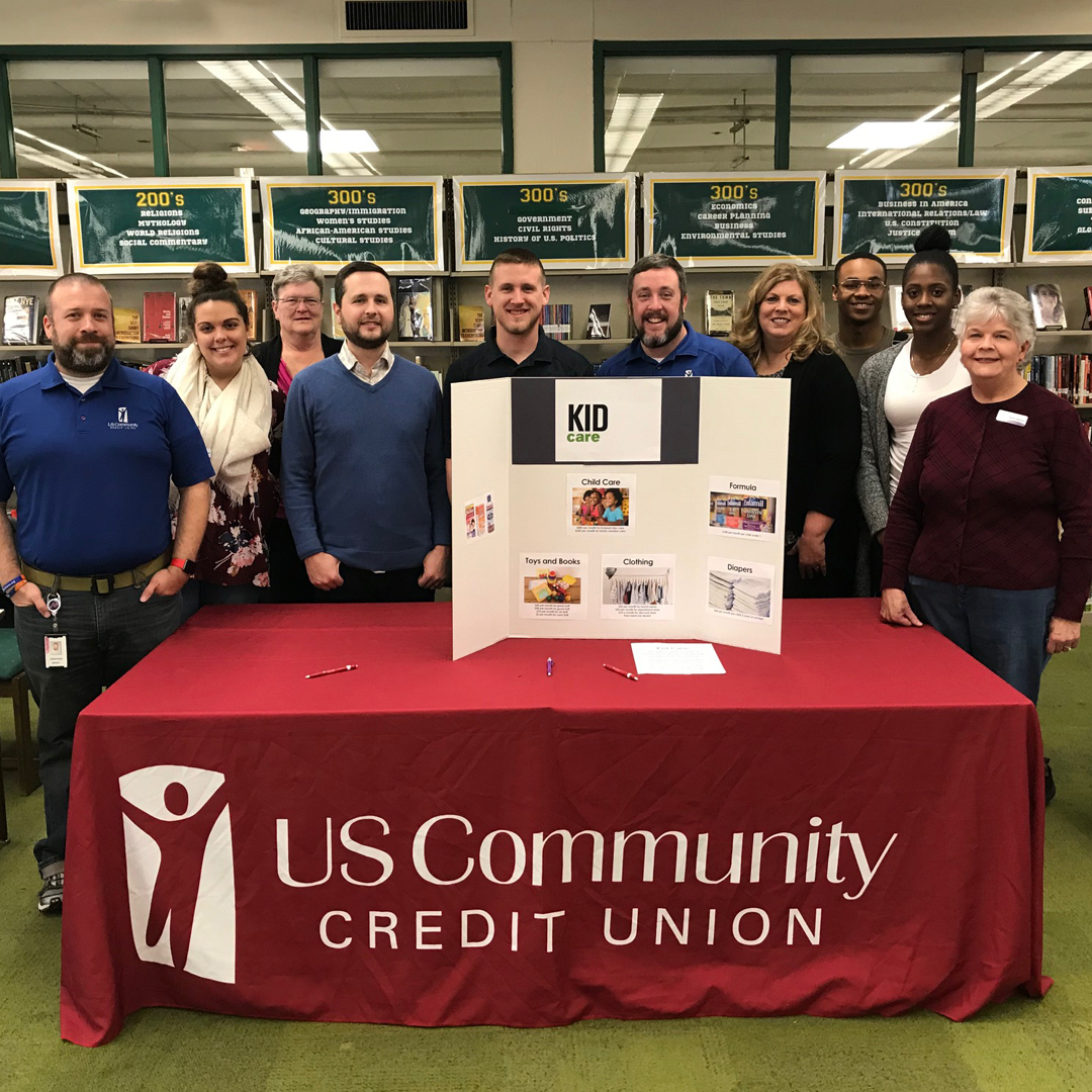 "A group photo of USCCU employees in front of a table with a sign reading ""US Community Credit Union"""