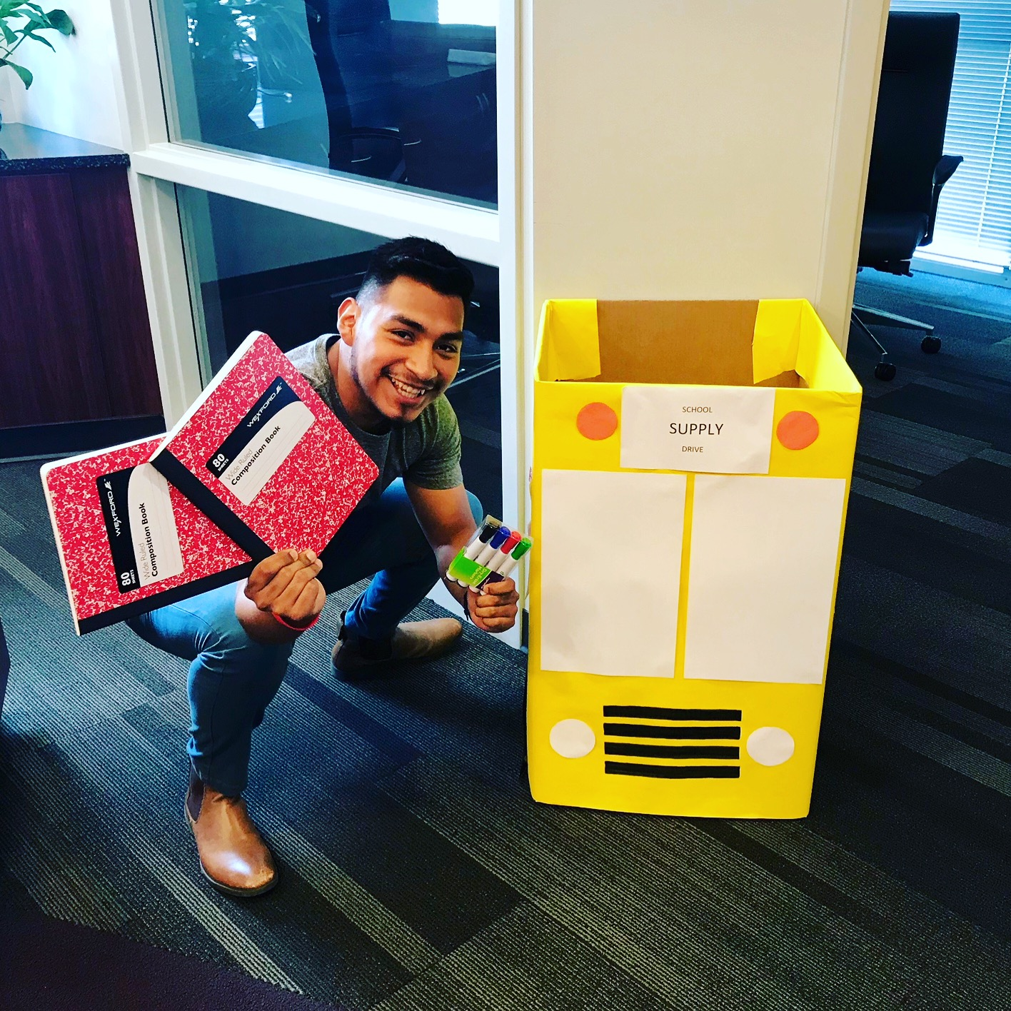 A smiling man holding pens and notebooks in front of a school donation bin.