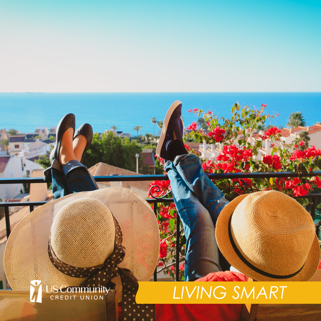 Two people relaxing on terrace overlooking ocean while on summer vacation wearing large hats. This photo is for the 10 things to do before your summer getaway blog from US Community Credit Union.