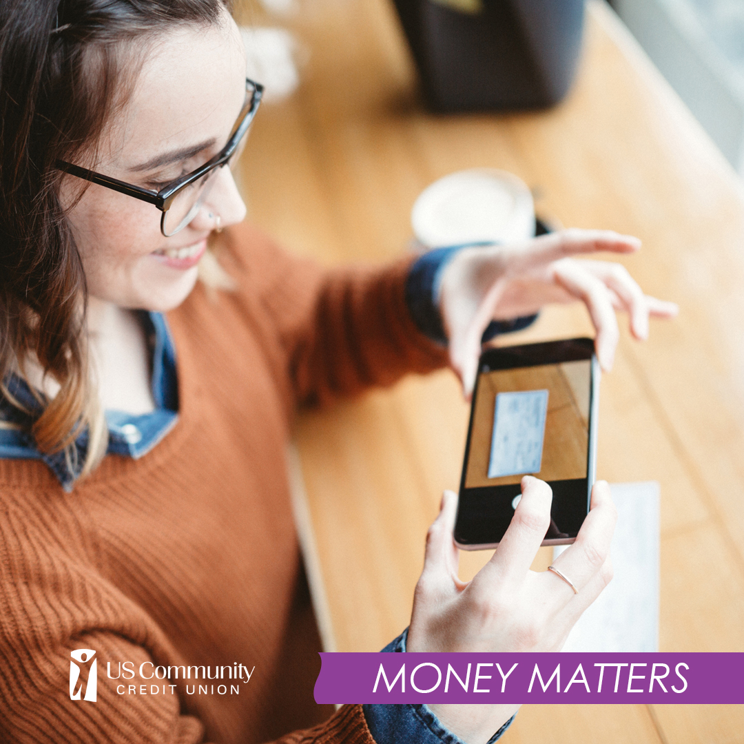 Girl sitting at table depositing check using her phone on the US Community Credit Union app.