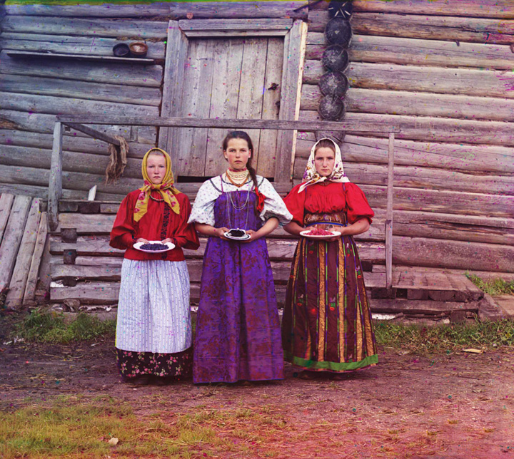 """Peasant girls. Three young women offer berries to visitors to their """"izba"""", a traditional wooden house, in a rural area along the Sheksna River, near the town of Kirillov, Russia. 1909."""
