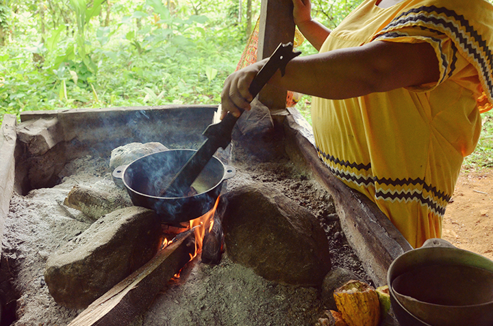 Woman tends to the roasting cocoa beans
