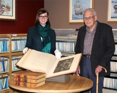 Associate Director of the Maritime Museum of British Columbia, Brittany Vis (left) with Don Hope (right) along with the donation of the 1785 Cook Journal and folio. Image provided courtesy of the Maritime Museum of British Columbia.