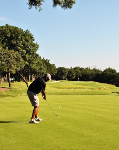 Kenny hits his tee shot to the par 3 third hole green.