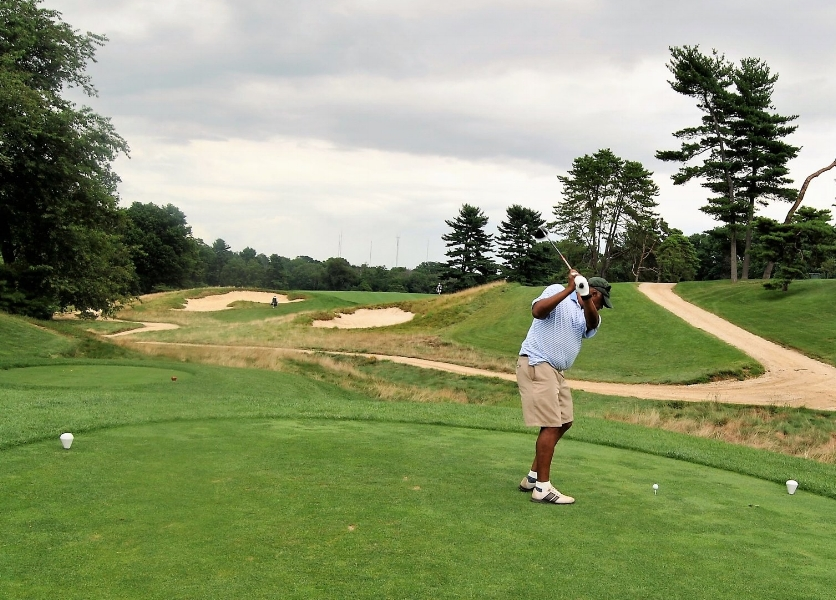 Malcolmn hits his tee shot on the fourth hole.