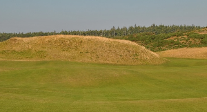 The mound in front of the 16th green. The aiming pole is just slight right of center on the mound. y call is in the middle of the fairway, 165 yards from the middle of the green.