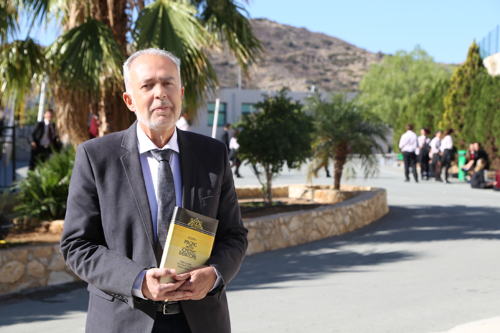 Dr Kouris at The Heritage Private School holding a copy of the book he co-authored on physics