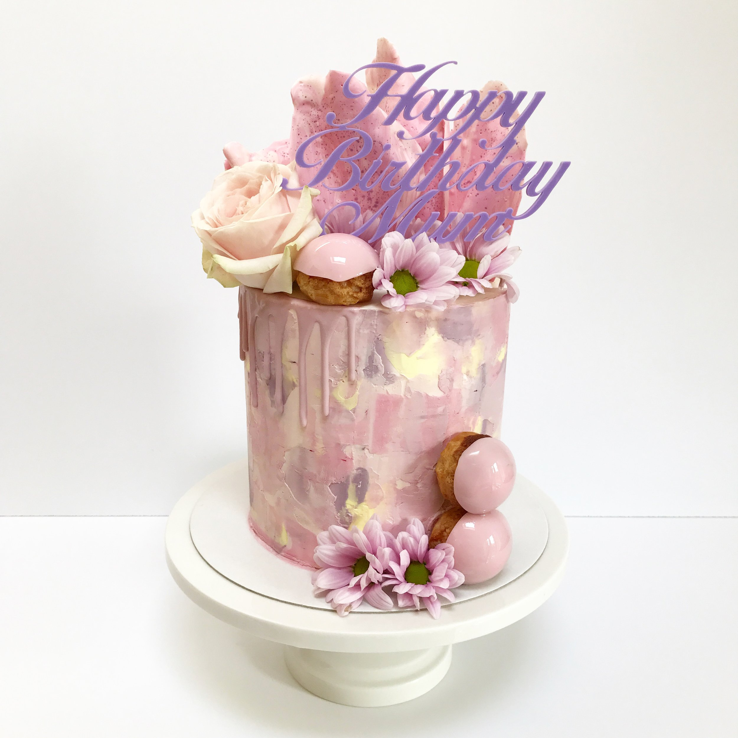 Pink, mauve, purple and yellow buttercream drip cake with chocolate sail and choux buns.JPG