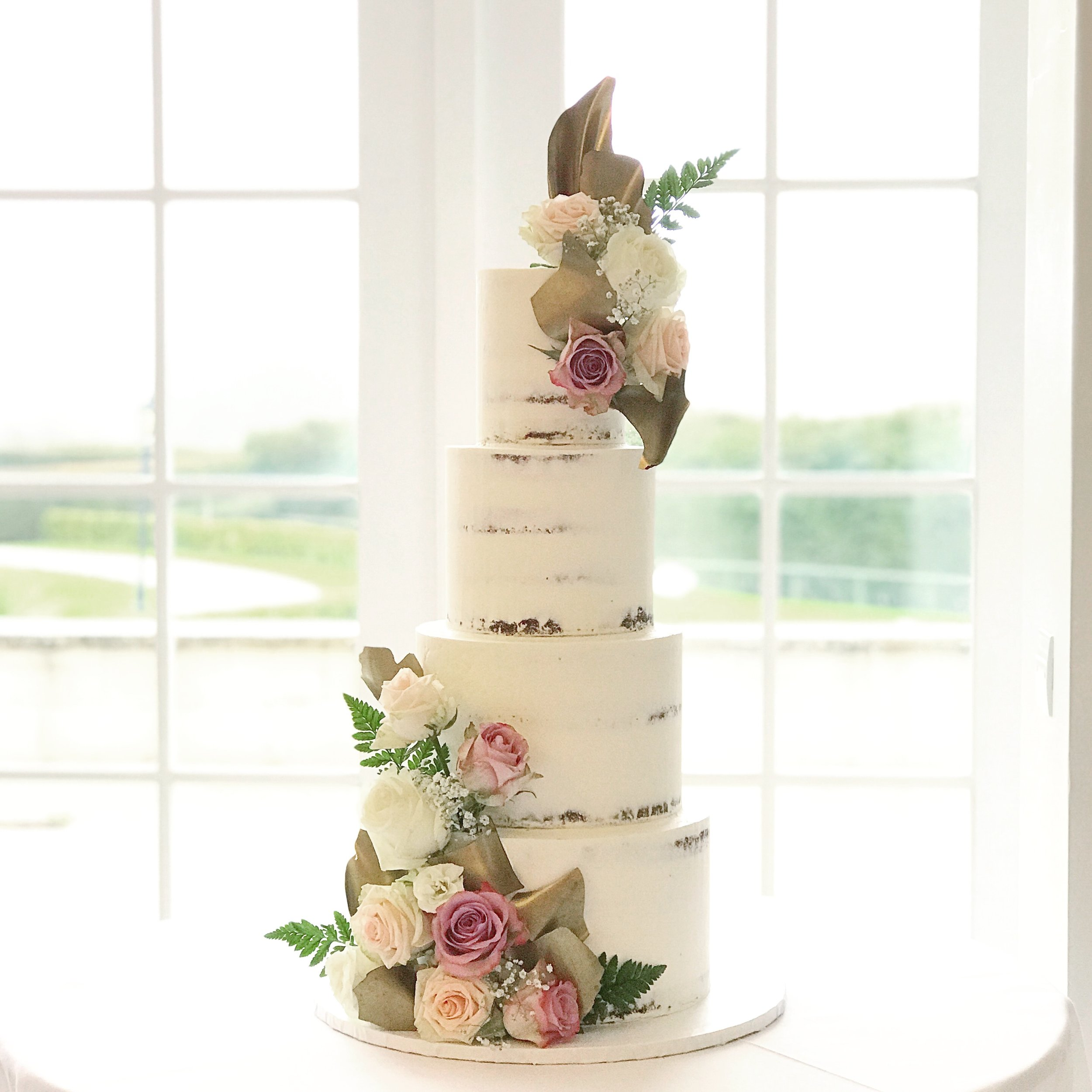 Four tier semi-naked cake with flowers and gold chocolate shards.JPG