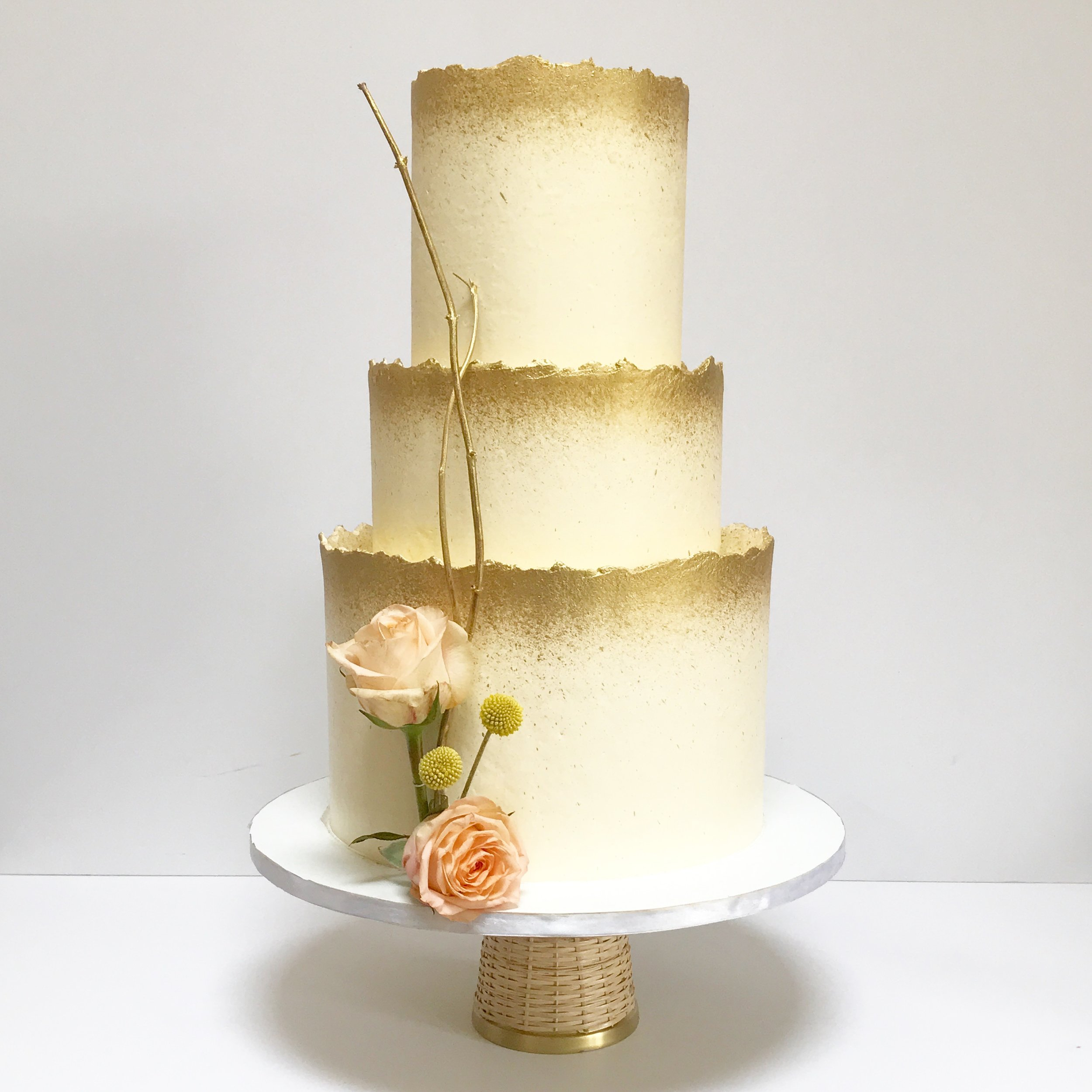 Three tier buttercream cake with rough edges and gold spray.jpeg