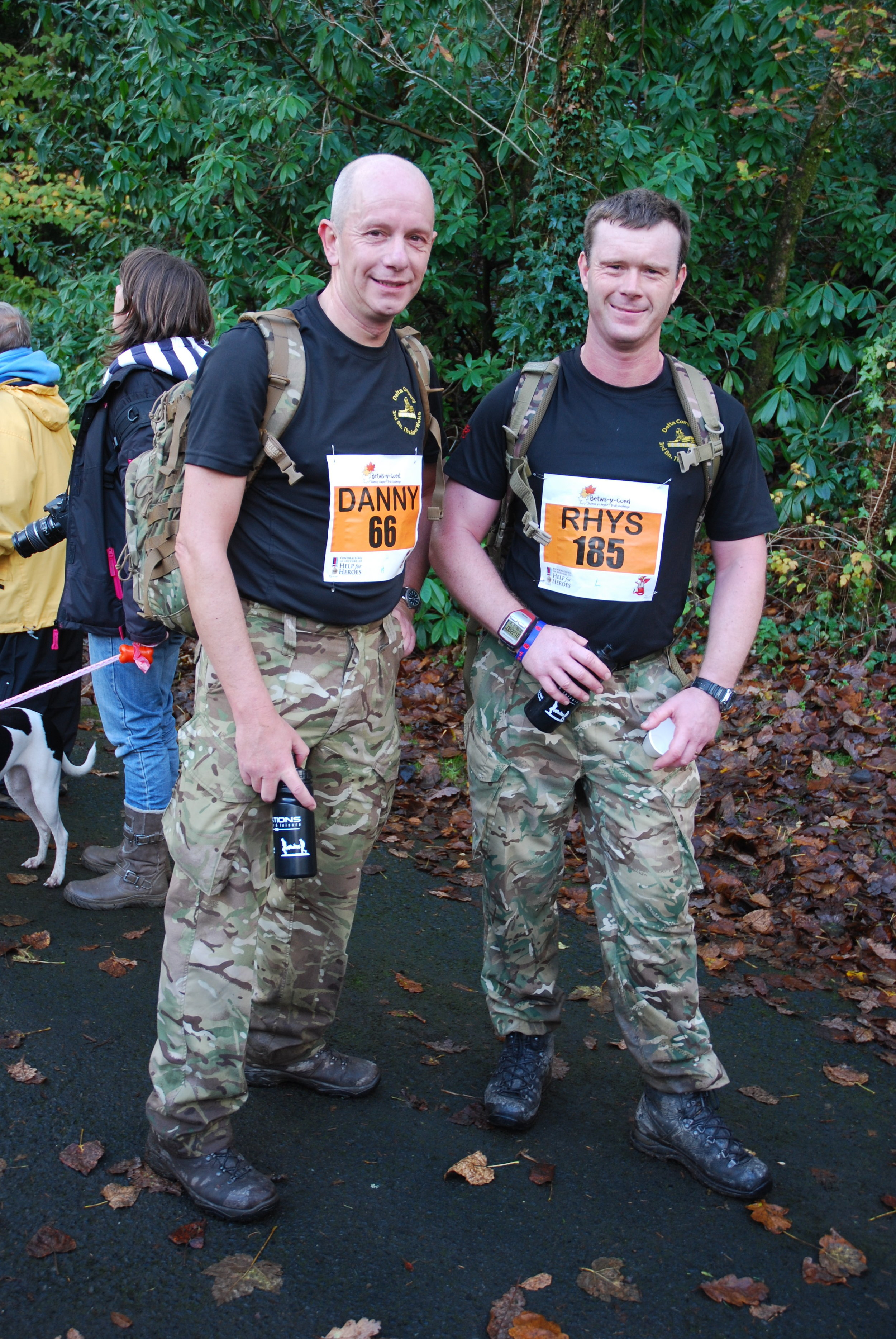 Two men in army clothing wearing their bergens ready for the bergen challenge.
