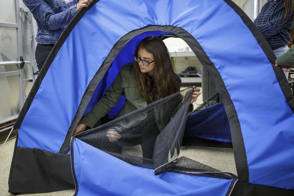 Paulina Martinez đang gắn dây kéo cho cửa của chiếc lều năng lượng Mặt Trời mà nhóm bạn vừa hoàn thành. Ảnh: Scott Witter/Mashable.
