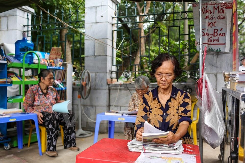 Những ngày trời nắng gay gắt, tại Gò Đống Đa (Hà Nội) người ta đã quen với hình ảnh một bà lão mang sách, báo miễn phí niềm nở mời người qua lại đọc. (Ảnh: Minh Sơn/Vietnam)
