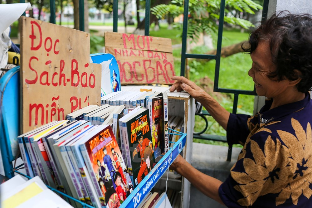 Kệ báo của bà Dung rất đơn sơ giản dị với một tấm biển ghi chữ: 'Mời nhân dân đọc báo – Đọc sách báo miễn phí' cùng rất nhiều quyển sách, báo mới có, cũ có. (Ảnh: Minh Sơn/Vietnam)