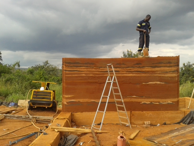 Công nhân đang nén đất trên một bức tường đất nện