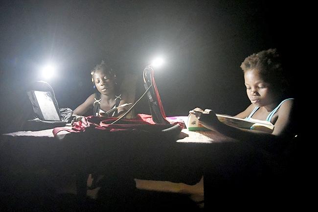 2 chị em Marie-France đang học bài nhờ nguồn sáng phát ra từ những chiếc ba lô năng lượng mặt trời Solarpak.