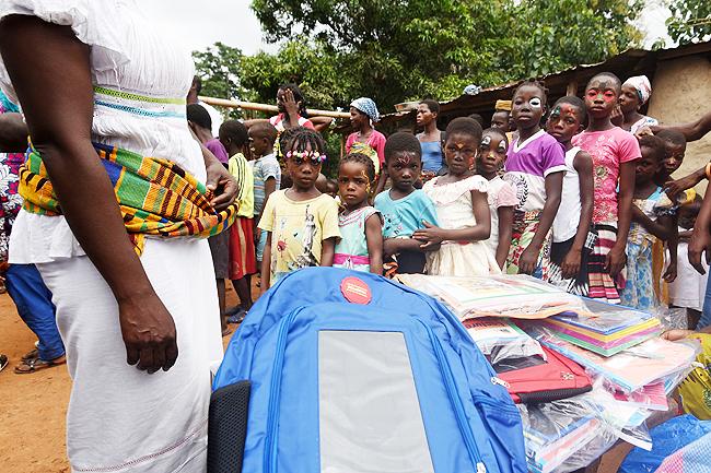Trẻ em Bờ Biển Ngà xếp hàng nhận chiếc đèn thắp sáng bằng những chiếc pin năng lượng mặt trời gắn trong chiếc balo Solarpak.