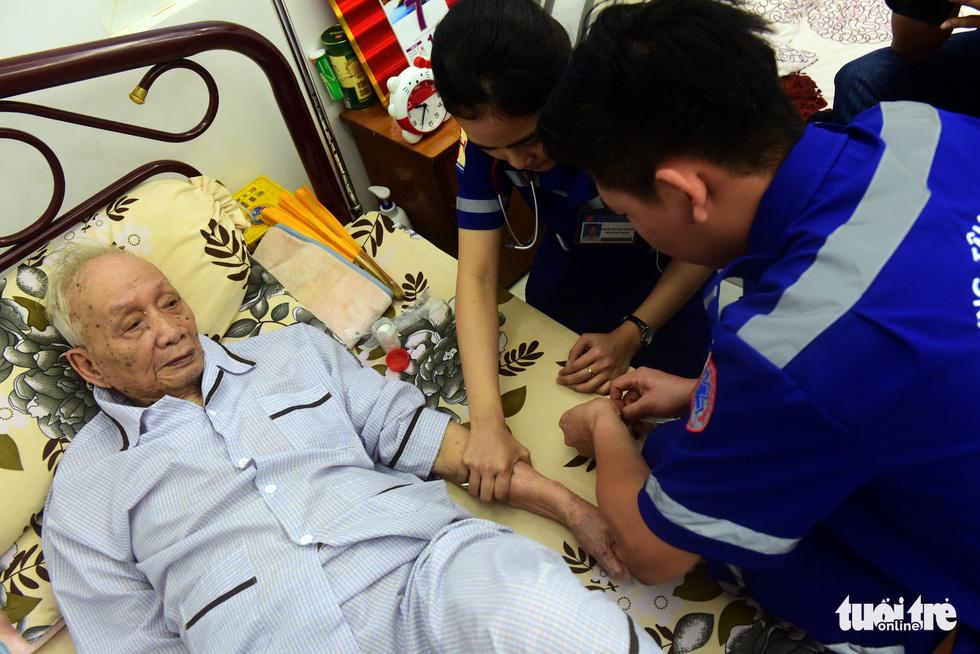 Cụ ông Nguyễn Tám (92 tuổi, Q.1, TP.HCM) được các bác sĩ cấp cứu tại nhà - Ảnh: Duyên Phan.