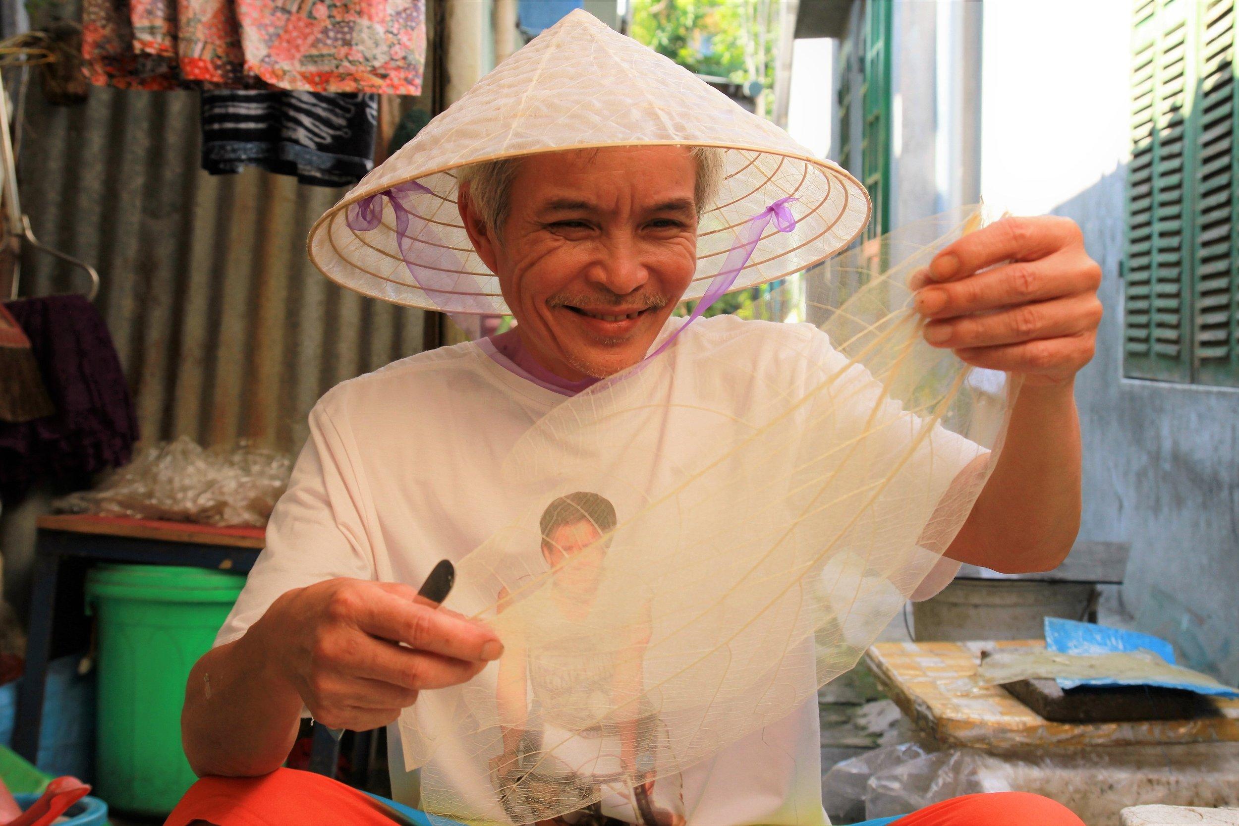 Ông Võ Ngọc Hùng tỉ mỉ làm ra những chiếc nón lá bàng tinh xảo. Ảnh: Nhật Tuấn.