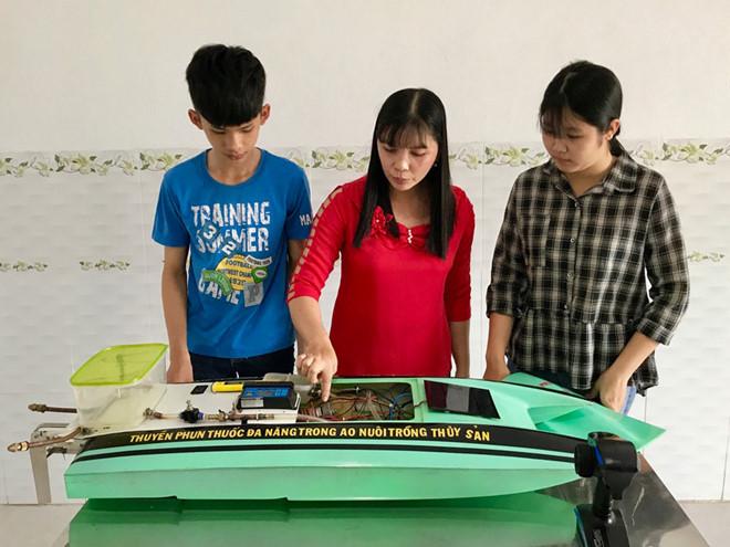 Cô giáo hướng dẫn và hai học sinh sáng chế thuyền phun.