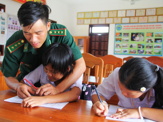 Thượng úy Lê Văn Chính hướng dẫn học sinh viết chữ.