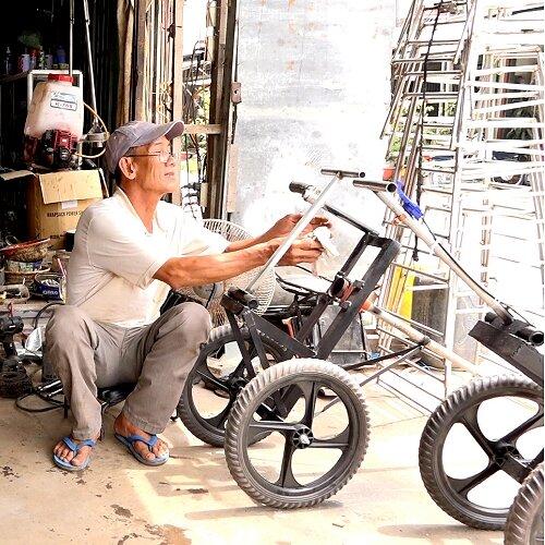 Ông Phạm Văn Đậm bên máy cắt cỏ do mình sáng chế .