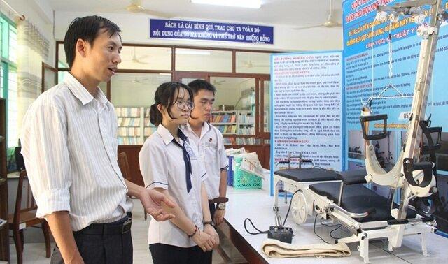 Em Nguyễn Thiện Luận cùng em gái Nguyễn Thị Bích Liên và thầy Nguyễn Văn Đồng bên chiếc ghế kéo cột sống cổ đa năng.