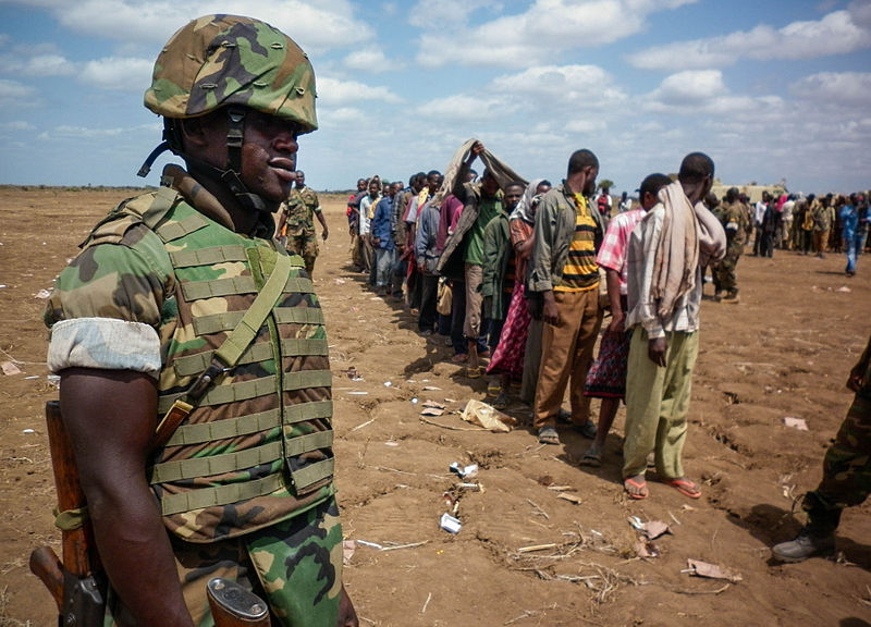 A Ugandan soldier of the African Union Mission in Somalia (AMISOM) looks on as members of Al-Shabaab stand in line after more than 200 fighters gave themselves up to AMISOM forces in 2012