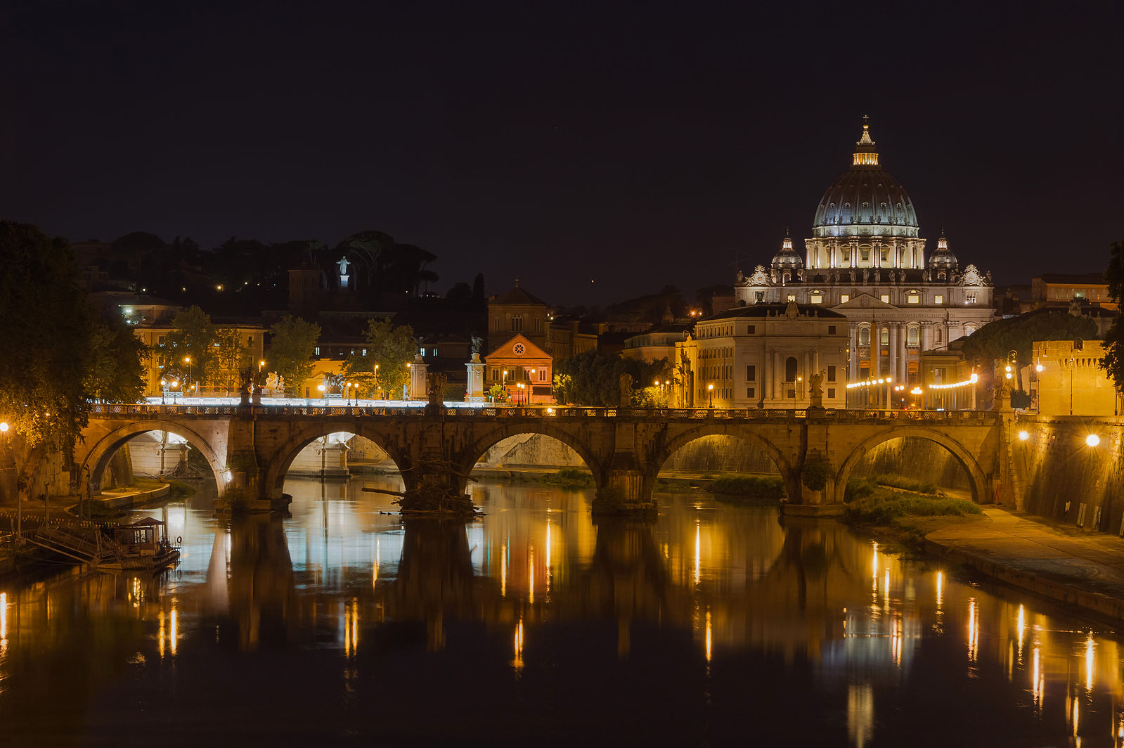Saint Angelo Bridge over the Tiber River with the St. Peter's Basilica in the background. Rome, Italy.