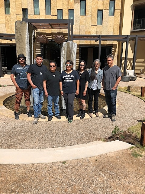 A group photo of all seven artists in Hotel Chaco's serenity garden. From left to right:  Ira Lujan ,  Adrian Wall,   Rhett Lynch,   Penny Singer,   Tammy Garcia,   Karen Clarkson,  and  Mateo Romero.