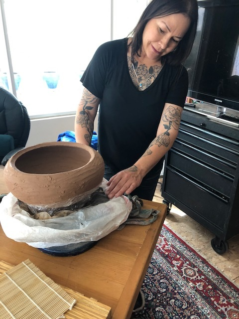 Tammy Garcia  showcasing a pot in the coiling stage.