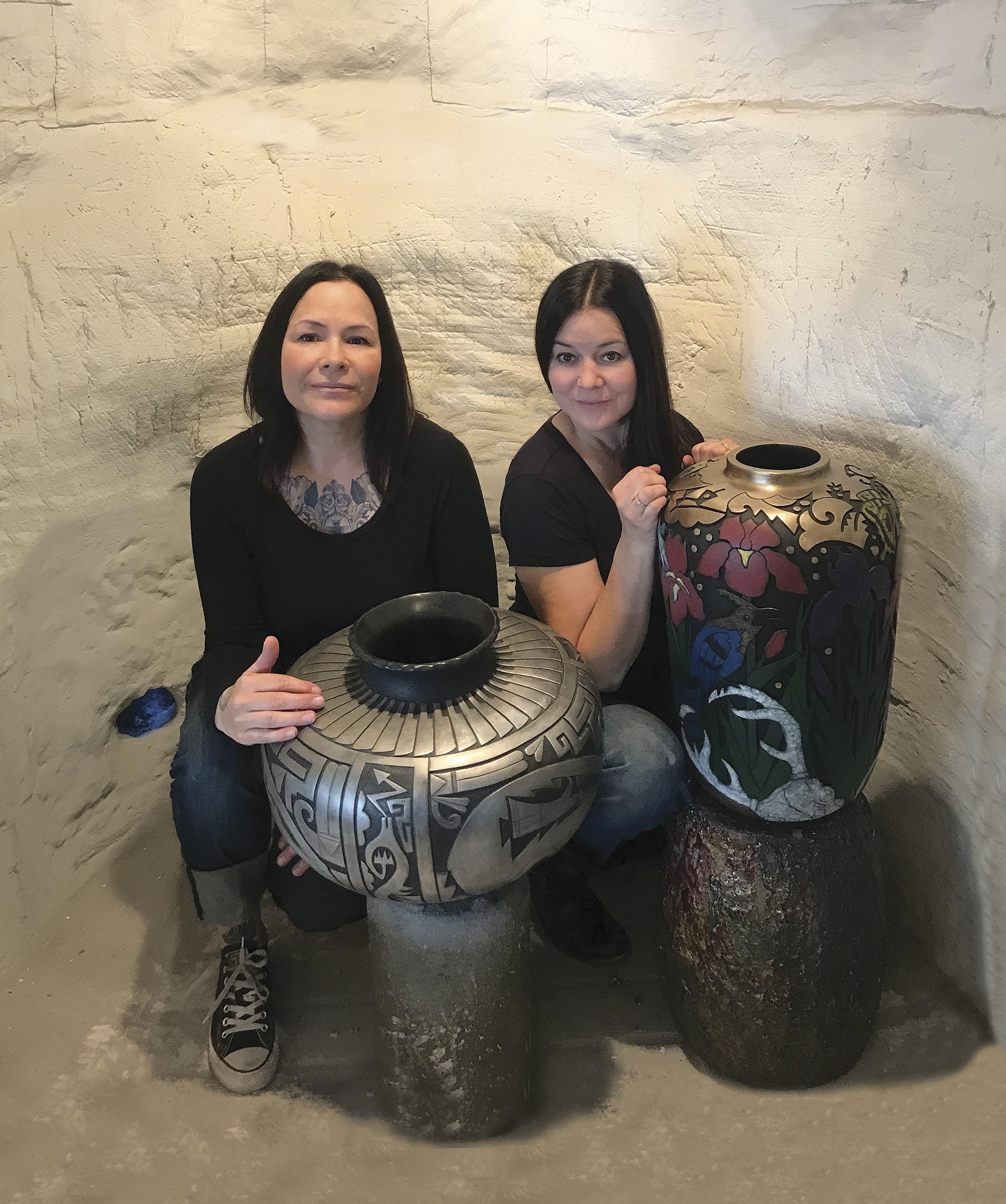 "Sisters  Tammy Garcia  and  Autumn Borts-Medlock  posing with their bronze pieces ""When The West Was One"" and ""Stellar's Day."""