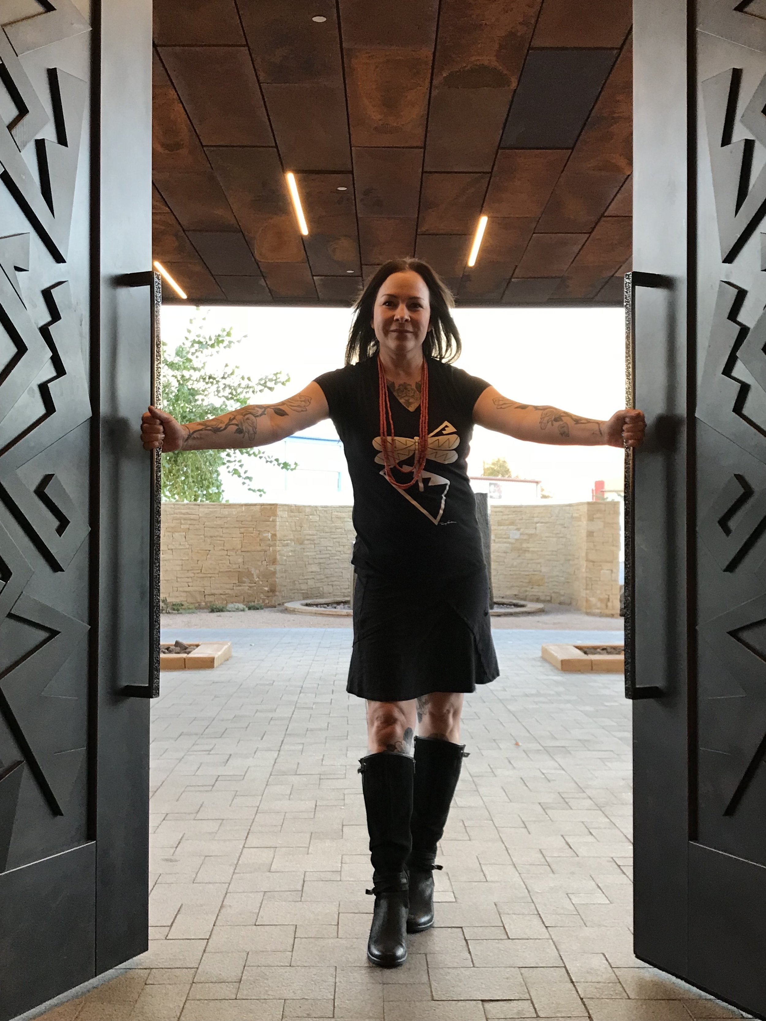 Tammy Garcia  posing with  the front doors she designed at Hotel Chaco.