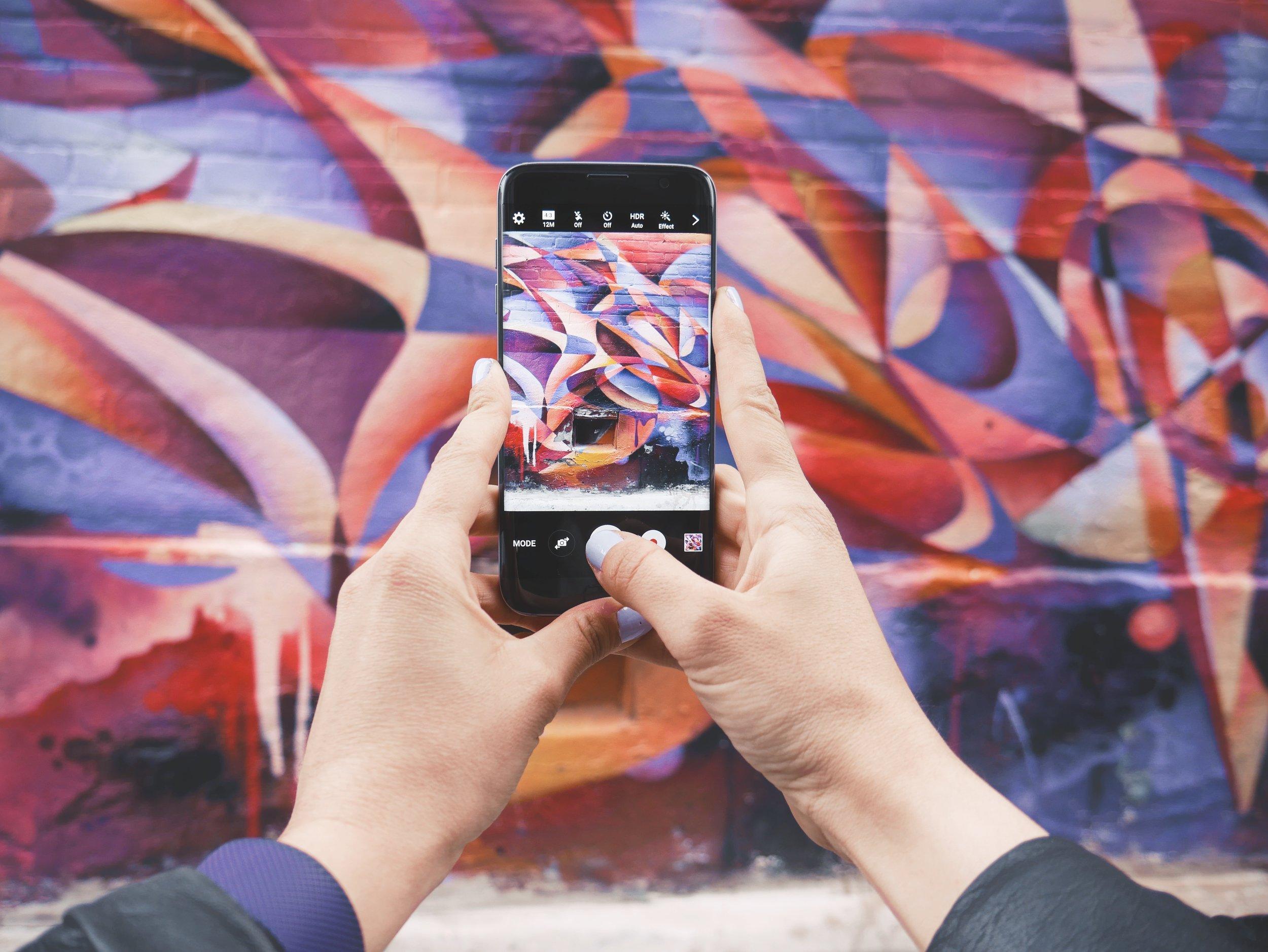 Smart phone taking picture of graffiti mural