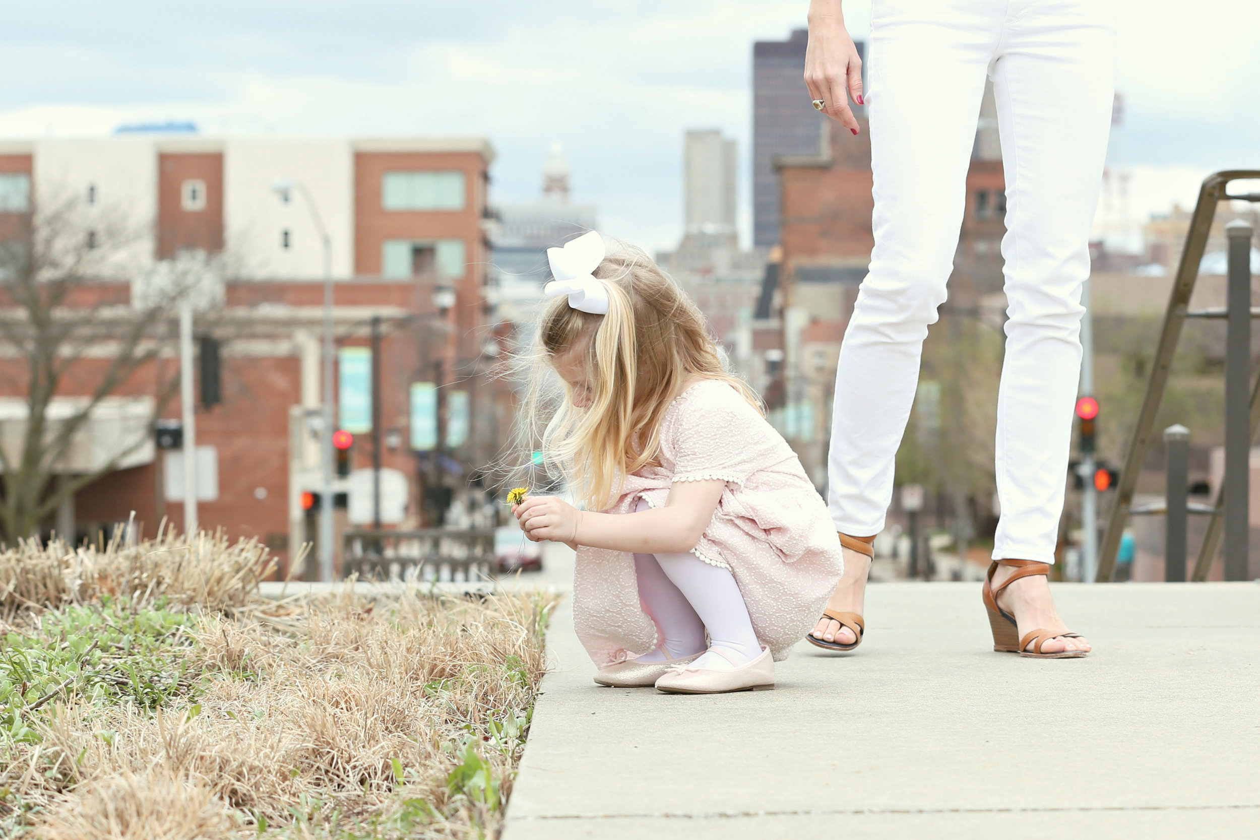Fashion blogger, Lady and Red's daughter R picking dandelions during a photoshoot | LadyandRed.com