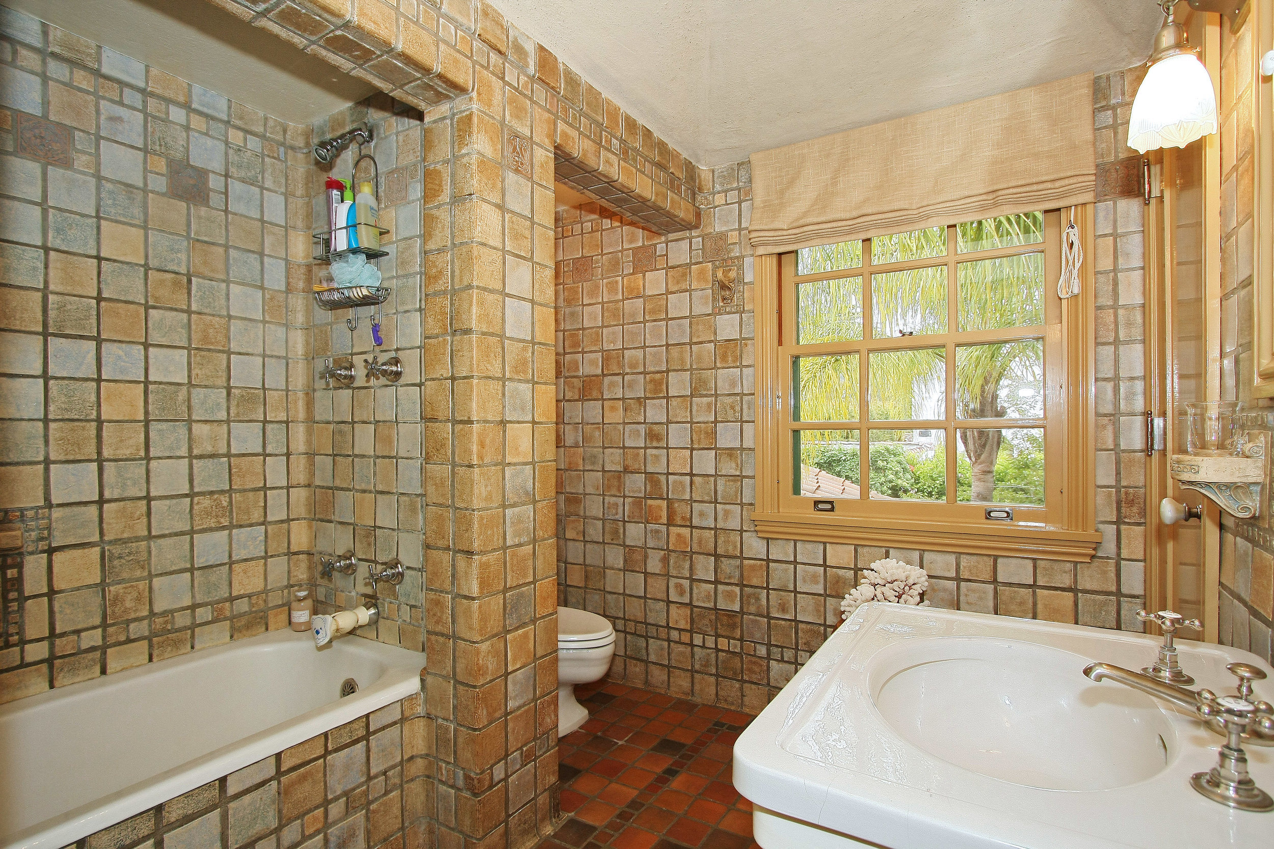 The master bathroom had the original floor to ceiling Batchelder tile including some rare decorative tiles. The coved ceiling has a special sanded plaster finish. The fixtures are new but look vintage.