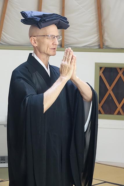 Kikuu recites the robe chant before putting on the okesa.