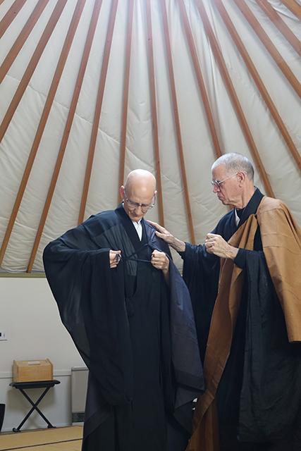 Hakuzan assists Kikuu in putting on the okesa.