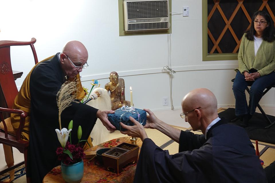 Daishin Sensei gives Kikuu the oryoki bowls.