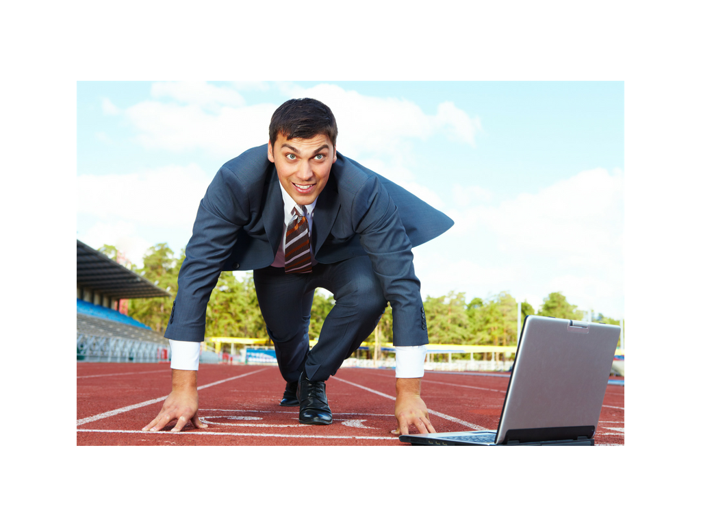 Business owner dressed in business tux in racing position on a professional running track