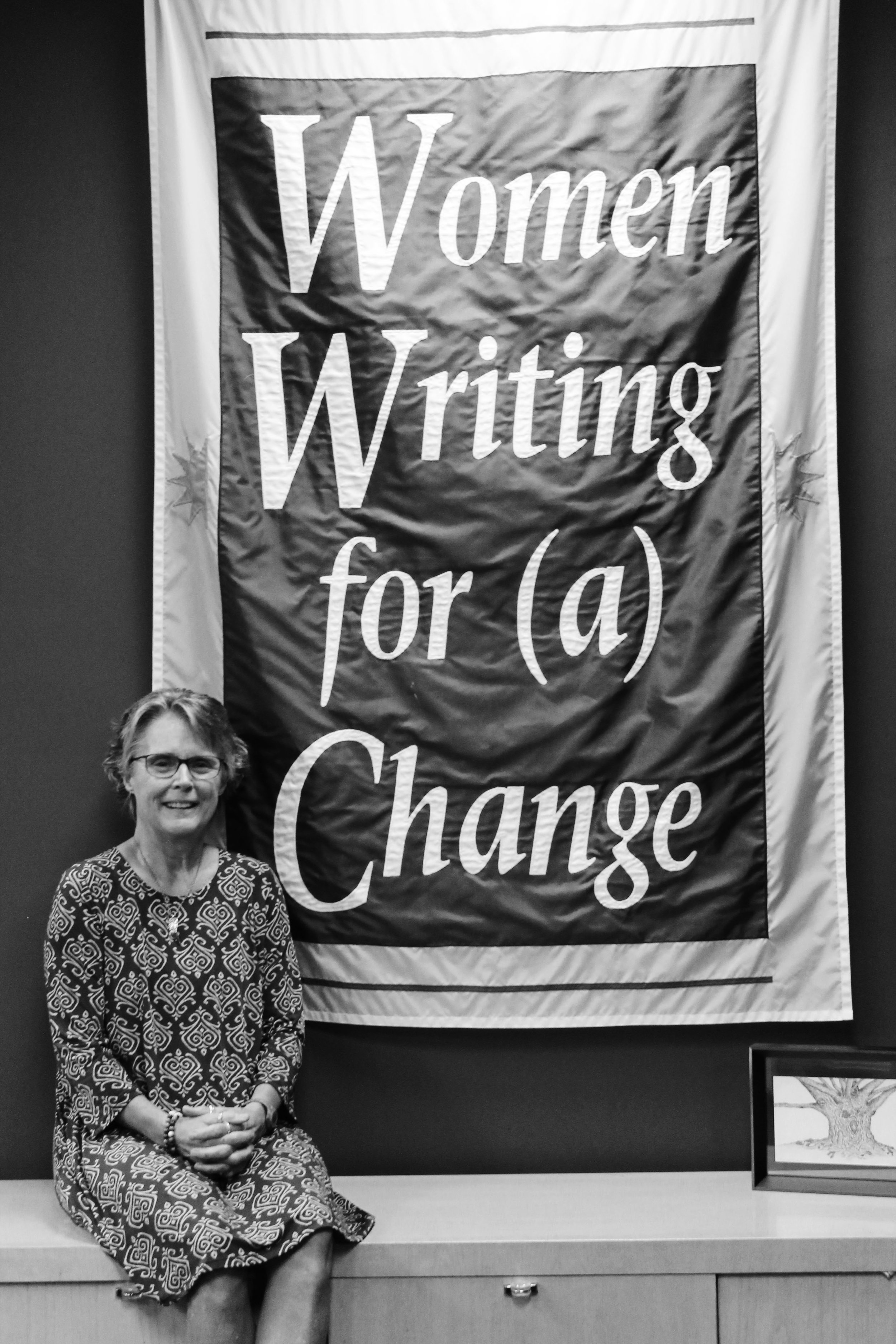 Laurie poses with a beaming smile in front of a Women Writing for a Change sign.