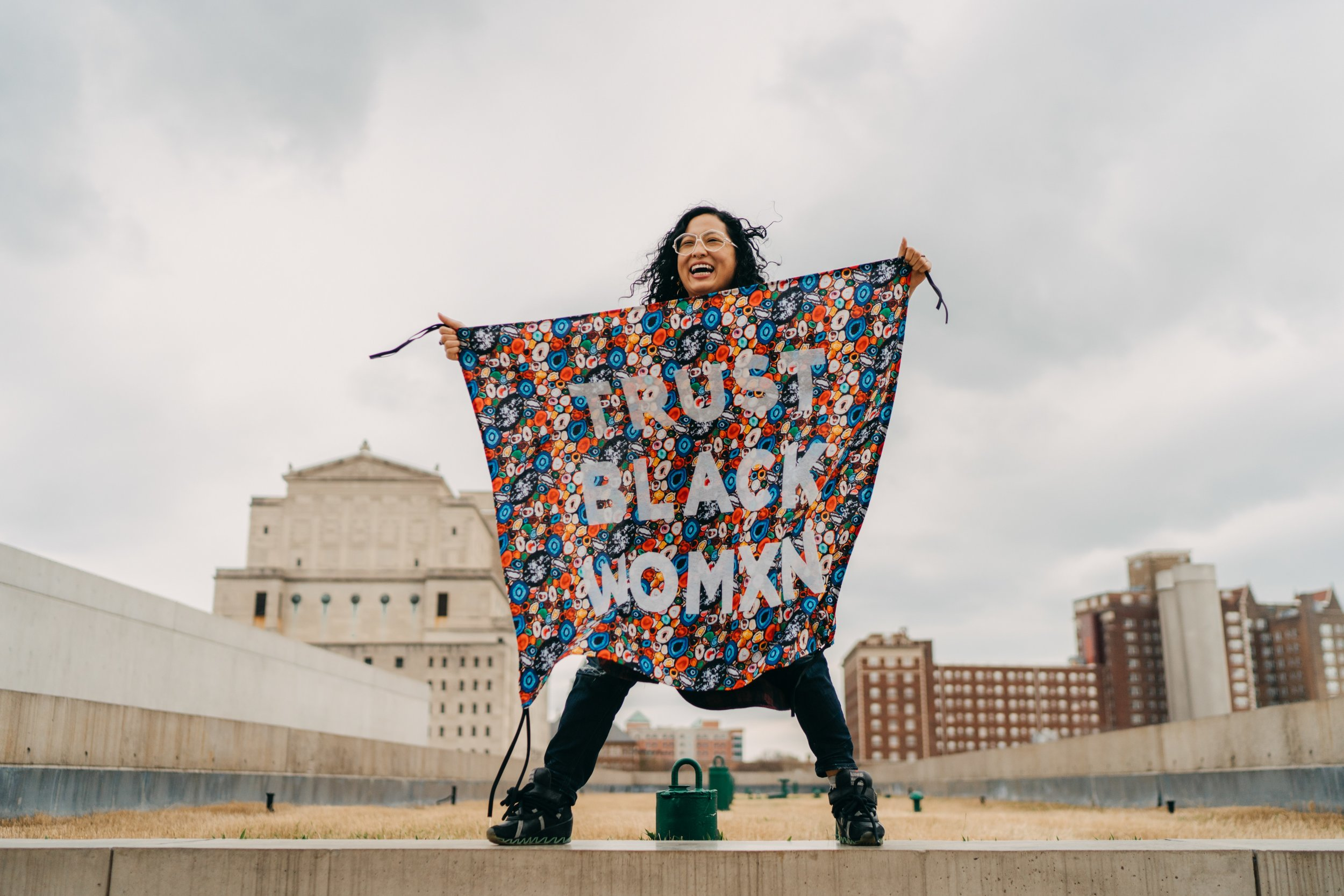 """""""Protest Banner Lending Library,"""" 2018. Aram Han Sifuentes holding a banner that reads """"TRUST BLACK WOMXN"""" on a rooftop. Photo by Virginia Harold. Courtesy of the Pulitzer Arts Foundation."""