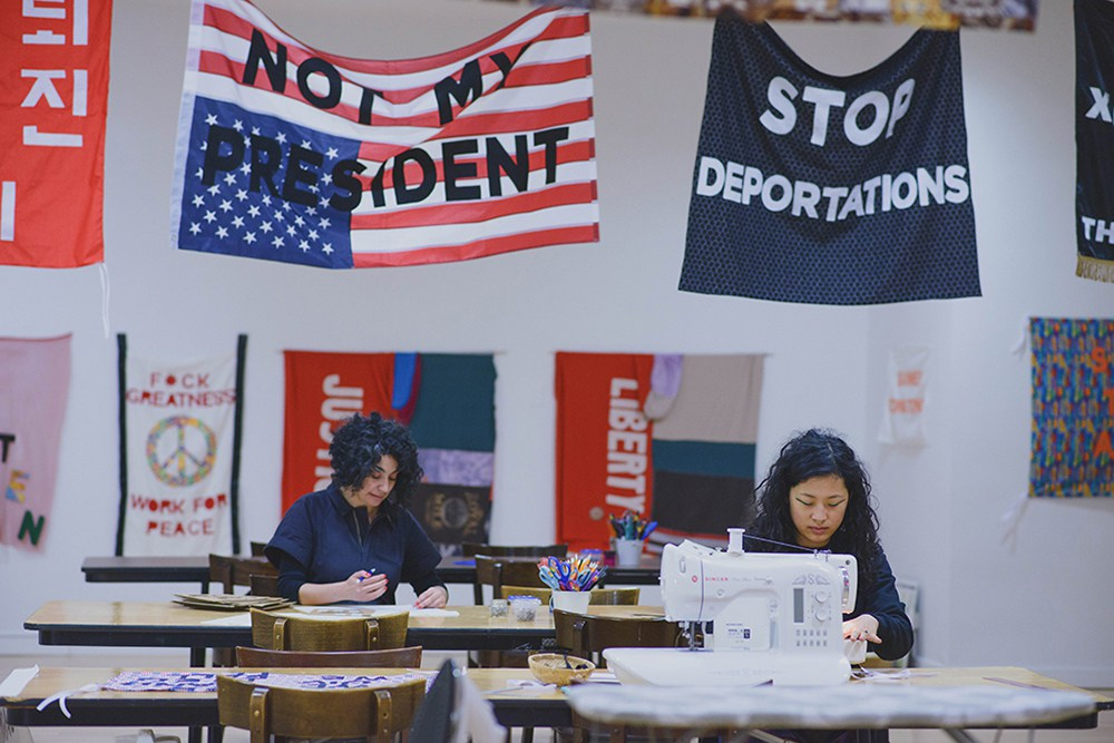 """""""Protest Banner Lending Library,"""" 2016–present. Aram Han Sifuentes and a participant at different tables sewing at the Chicago Cultural Center with protest banners hanging above them that read """"NOT MY PRESIDENT"""" and """"STOP DEPORTATIONS."""" Photo by eedahahm."""