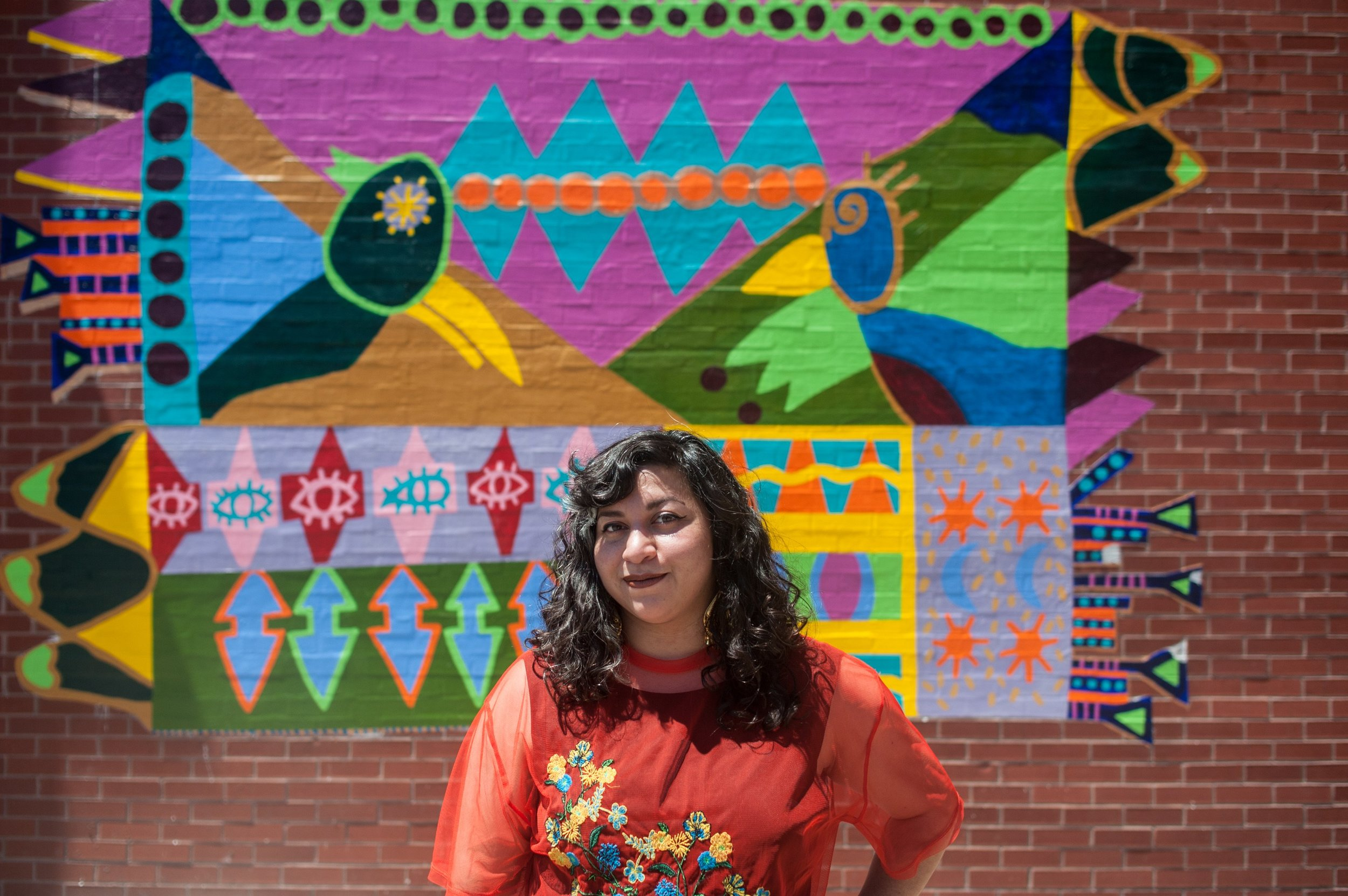 """Featured Image:Victoria Martinez standing in front Pickard Elementary in Pilsen near a mural she painted collaboratively with 5th thru 7th graders from the school. The mural """"Championing Neighborhood Memories"""" was inspired by the permanent collection from the National Museum of Mexican Art and is located on the Pickard playground. Martinez, who attended the school from Kindergarten thru 8th grade, recurrently works with these students. Photo by William Camargo."""