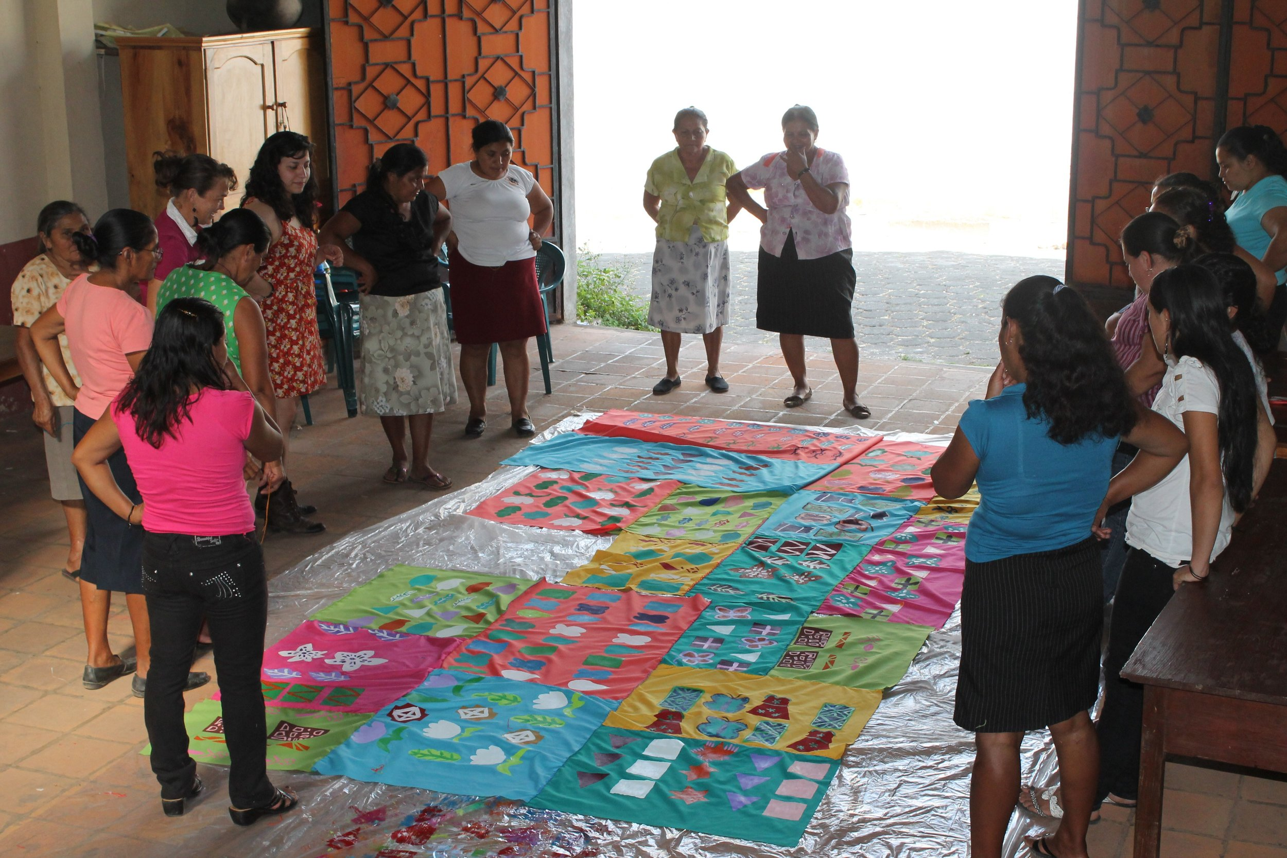 """""""Morazán Hilvanando Colores,"""" 2013. Fiber collaboration at Walls of Hope in Perquín, El Salvador. Victoria Martinez is standing with a group of women around a large textile on the floor. The textile is composed of different rectangular fabric pieces of varying vibrant colors that have a range of geometric patterns painted onto them. The piece was collaboratively made by the artists and these women, who have experience with war in El Salvador, from being nurses at war to having relatives to past survivors. Image courtesy of the artist."""