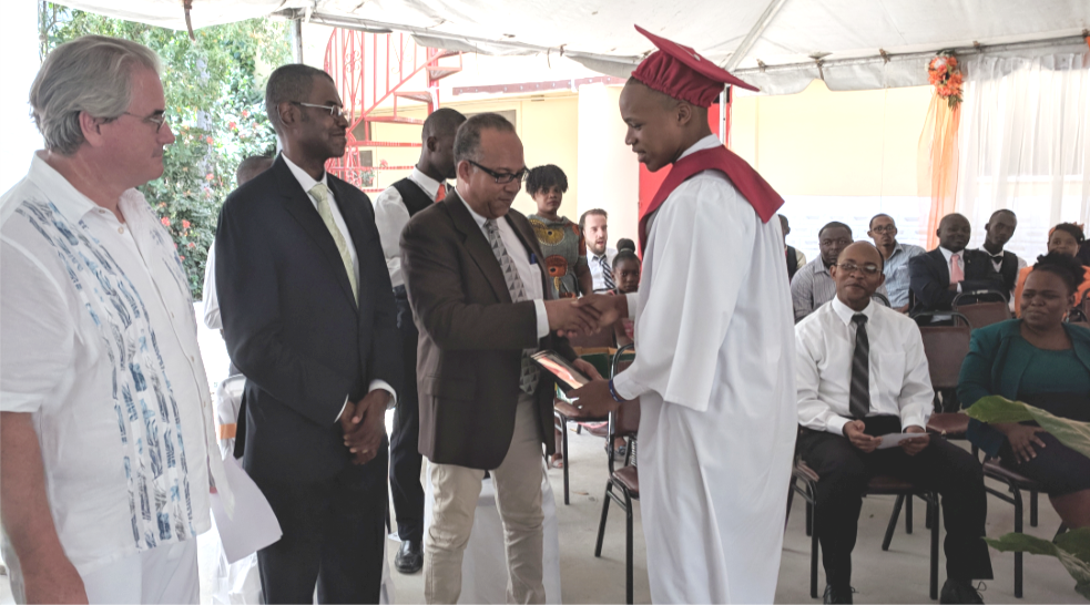 THP Board Vice Chair & Chair of THP's Partner Foundations in Haiti Patrick Brun (center), with class godparent René Jean Jumeau (second from left) and THP President Deacon Patrick Moynihan (far left), presents Jacques Briand Louis with his diploma at LCS' 23rd Graduation Ceremony on Saturday, June 16, 2018.