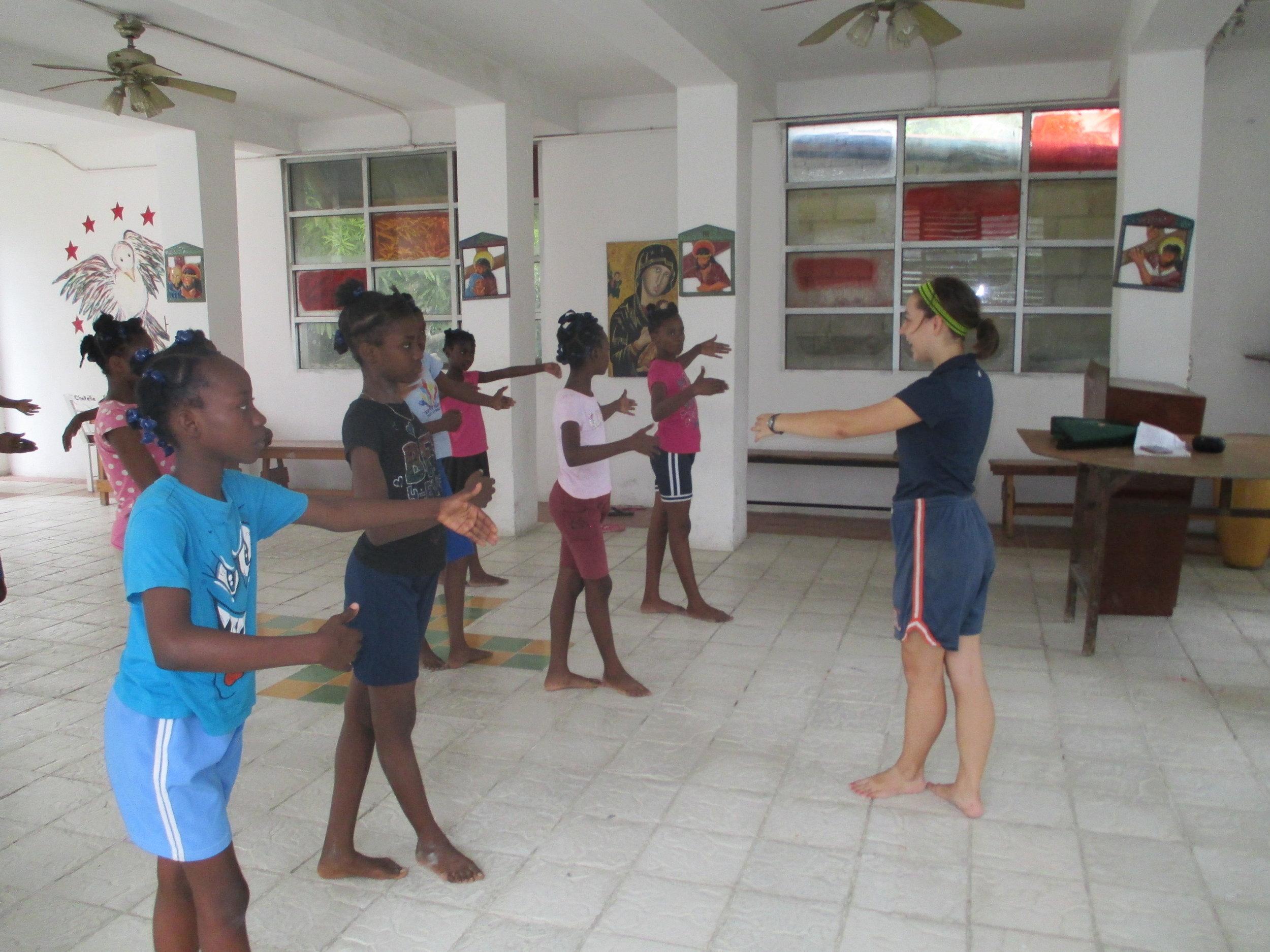 Volunteer Abigail Knapp leads Dance Club during Play Hour .