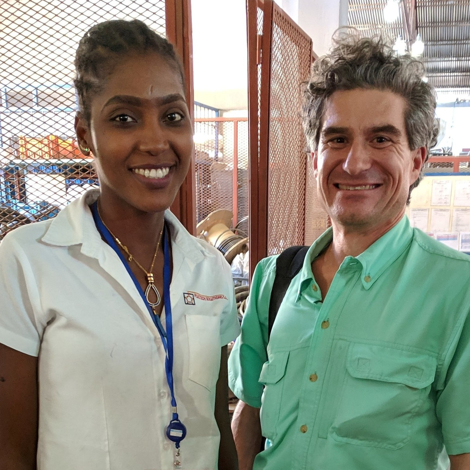 Louverture Cleary School graduate Jesula Tintin ('07) takes a moment to greet Jimi Grondin (THP Volunteer Alum '01-'02) during a recent tour of Plastech Solutions S.A. in Haiti.