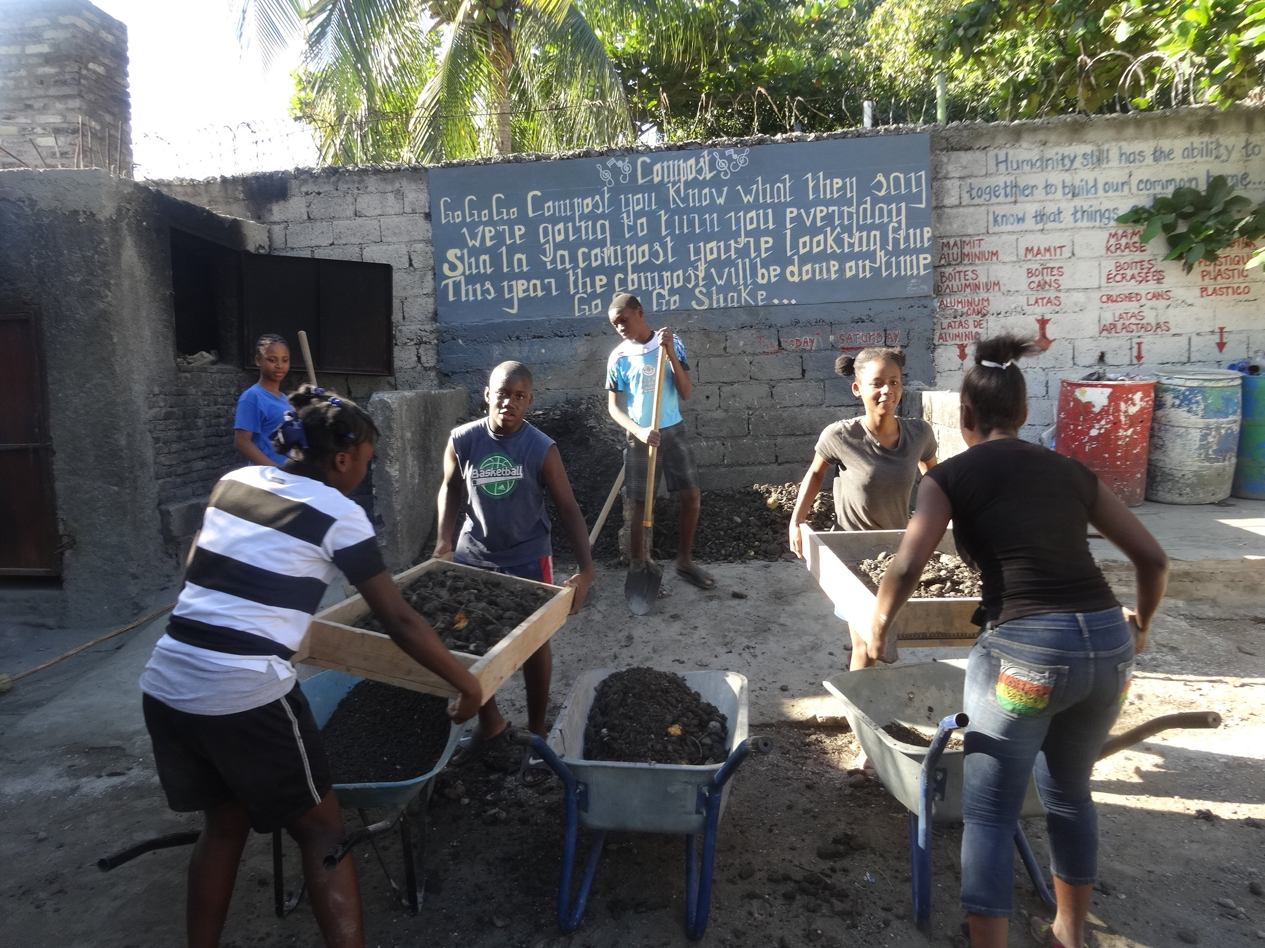 """Louverture Cleary School Santo 5 students divide waste from their campus into categories, each to be handled responsibly. Above the compost pile are lyrics to an LCS original song, """"Go, Go, Go Compost!"""""""