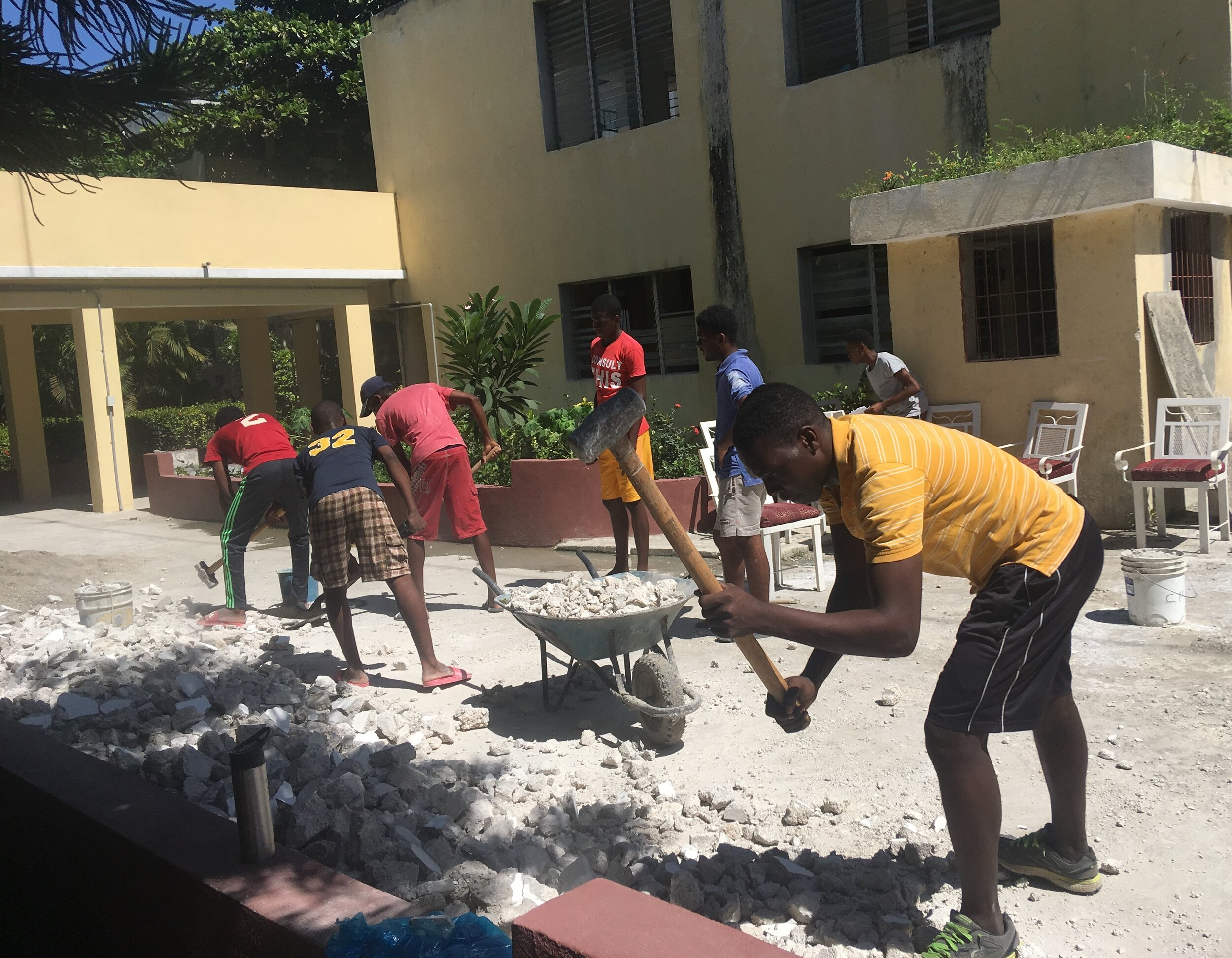 Keslin Augustin (LCS '16) works breaking rocks on the Louverture Cleary School Santo 5 campus.